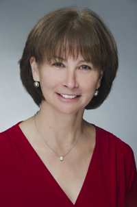 Headshot of Donna Martin in a red sweater with a gray background